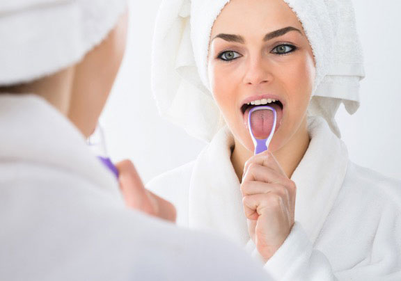Woman using a tongue cleaning tool